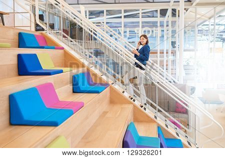 Businesswoman looking away while walking up a modern staircase in a colourful creative office space, carrying a cup of takeaway coffee
