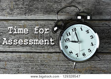 Black alarm clock on the rusty wooden table with word Time for Assessment
