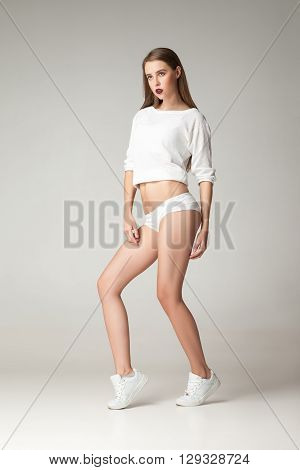 Portrait of young brunette in shirt, undies and sneakers posing against of white background