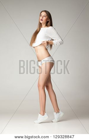 Young brunette putting off shirt while wearing undies and sneakers.Studio shot