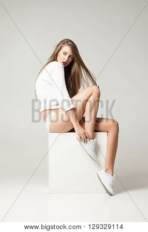 Portrait of young brunette looking away while posing on white cube in undies.Studio shot