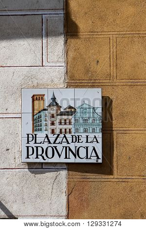 MADRID, SPAIN - MARCH 13, 2016: Closeup of the street sign in Madrid. They are hand-painted ceramic tiles typically composed within 9 or 12 tiles. They depict the name of the alley or street as well as illustrations that indicate special meanings.