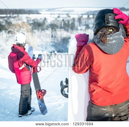 people in ski suit holding snowboards on a snowhill