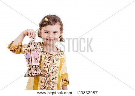 Ramadan Kareem - Young girl smiling and holding Ramadan lantern