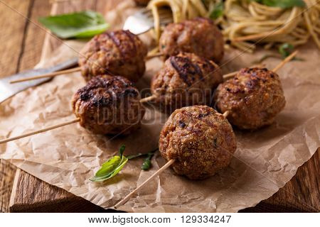 Turkey meatballs on wooden skewers with pesto pasta