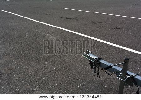 A trailer hitch waits for a vehicle in an empty parking lot.