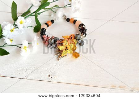 Beautiful female bracelet with stones, beads and flowers made of polymer clay on white wooden background with copy space for text