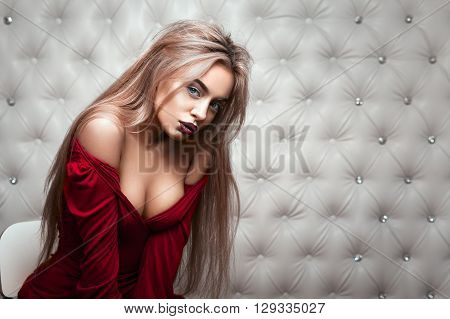 Studio portrait of a sexy blond in red dress, over leather upholstery background. Elegant luxury woman with a seductive neckline and bare shoulders looks into the camera.