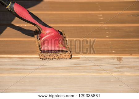 Staining a wooden deck with a staining pad.