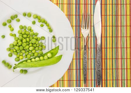 Fresh Green Peas On Plate With Fork And Knife Closeup, On Colorful Bamboo Placemat