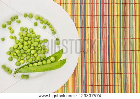 Fresh Green Peas On Plate, On Colorful Bamboo Placemat