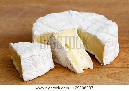 White Mould Cheese With Cut Slices Isolated On Wood Board.