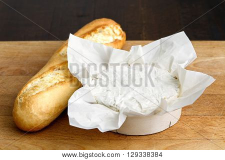 White Mould Cheese In Wrapping With Baguette On Wood Board.