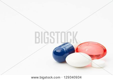 A variety of pharmaceutical pills and tablets on an isolated white background.