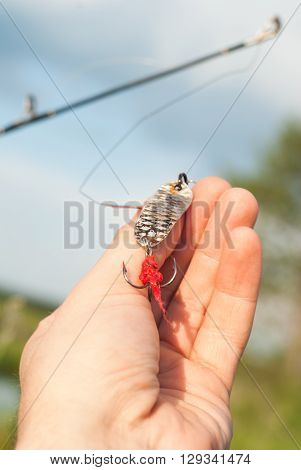 bait for catching predatory fish in hand on background of green grass