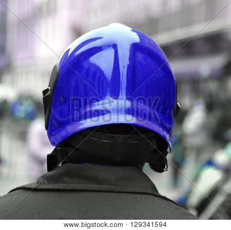 Policeman With The Blue Protective Helmet Controls The People