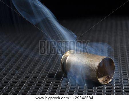 Empty handgun hull on a black grate and smoke rising