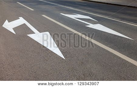 Road with white marking lines and direction of motion on asphalt