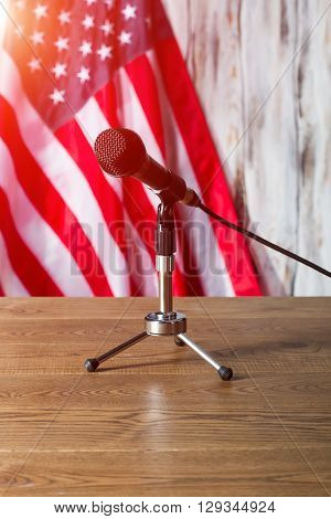 United States flag and microphone. Table with microphone beside flag. Broadcast will soon begin. Morning at the radio station.