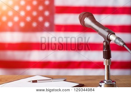 American flag, microphone and pen. Pen and paper beside microphone. Early morning at TV studio. Special guest will soon appear.