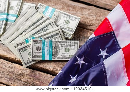 US flag and dollar bundles. Flag laying near cash bundles. Fruits of diplomacy. Freedom and wealth.