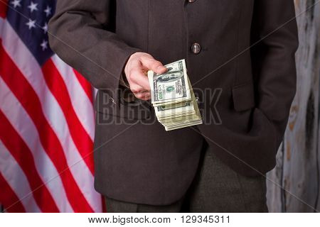 Man in suit holding dollars. USA flag, man and money. Such an interesting offer. I need powerful friends.