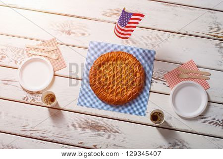 American flag, pie and drinks. Table flag beside round pie. Savoury breakfast in american cafe. Simple dessert served with coffee.