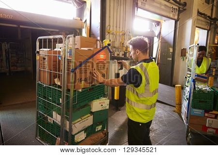 Man in a warehouse holds and scans a box for delivery