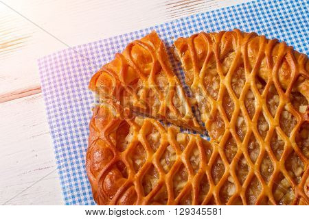 Sliced pie laying on napkin. Pie on white wooden background. Delicious pastry with fruit filling. Tasty organic meal.