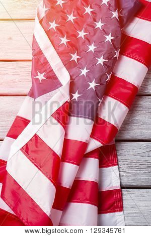 Creased USA flag under sunlight. Crumpled national flag of USA. Cherish every day of life. Democracy will lead the way.