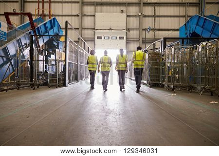 Four colleagues in reflective vests leaving a warehouse