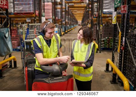Female warehouse manager instructing man on tow tractor