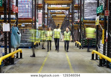 Staff in reflective vests walking to camera in a warehouse