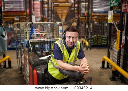 Man on tow tractor in distribution warehouse leans to camera