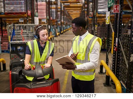 Warehouse manager instructing woman operating tow tractor