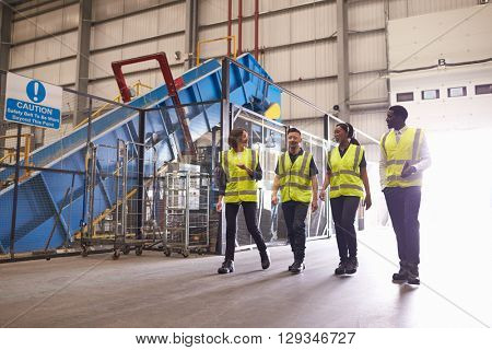 Staff wearing reflective vests in an industrial interior
