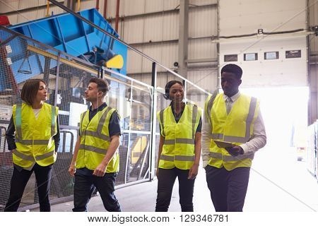 Supervisor and coworkers walking in an industrial interior