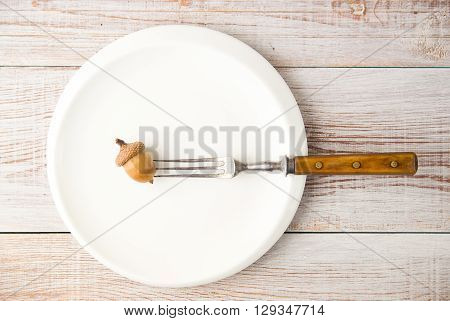 Acorn on a plate and fork on the table