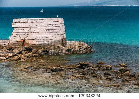 Ancient Marine Fortifications. Ruins Of Old Tower Into Mediterranean Sea In Tarifa, Spain. Tarifa Is The Most Southern Town Of Europe On The Strait Of Gibraltar