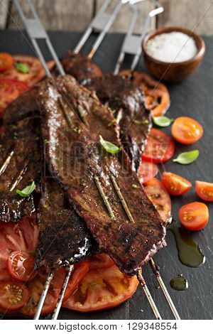 Flank steak on skewers with tomato salad