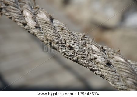 Slightly used frayed thick rope made of twisted beige strings