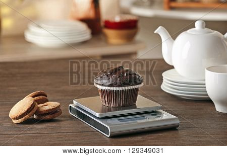 Chocolate cupcake and digital kitchen scales on wooden table
