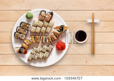 Japanese food restaurant, unagi sushi maki gunkan roll plate or platter set. Set for two with chopsticks, ginger, soy, wasabi. Sushi at wooden planks background. Top view, flat lay.