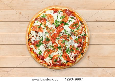 Delicious pizza with mushrooms, tomatoes and chicken ham - thin pastry crust at wooden round desk and wood background. Italian food. Top view