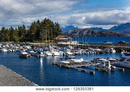 Berth boats in the Norwegian fjord on a background of blue sky and sea landscape