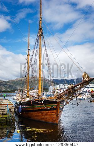 Ancient ship at the berth in the Norwegian fjord on a background of blue sky and sea landscape