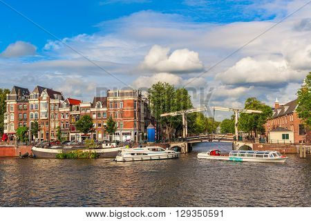 Boats on canal in front of small bridge and traditional houses under beautiful sky in Amsterdam, Netherlands.