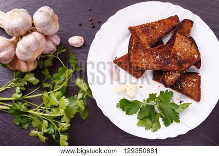 Roasted salted garlic croutons with fresh parsley and whole garlic on white plate.