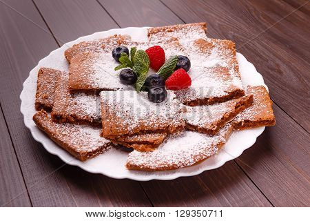 Honeyed cake with ginger dusted with icing sugar with raspberry bilberry mint on plate on wooden background