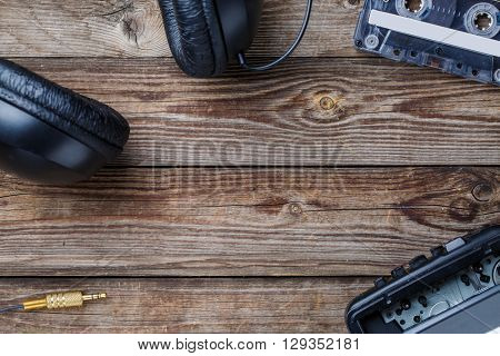 Cassette tapes, player and headphones over wooden table. top view.